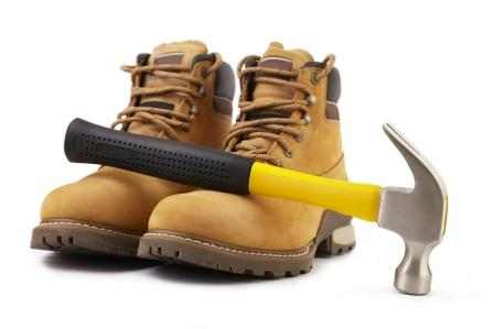 working boots and hammer isolated on white background selective focus